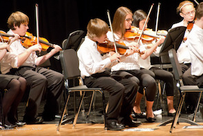 students performing in orchestra concert on stage