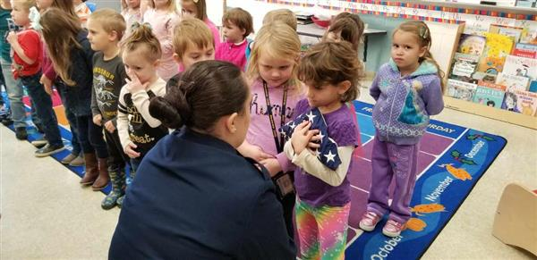 pre-k students learn to hold and fold flag