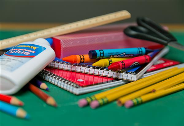 pencils, crayons, notebooks and glue laid out on table surface for school supplies