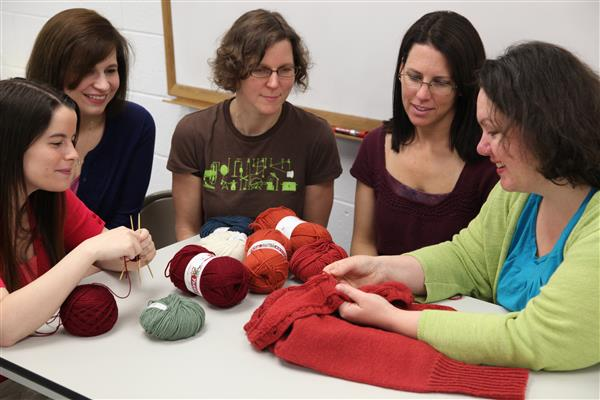 Students look on as instructor explains crochet techniques during class with Adult & Community Ed.