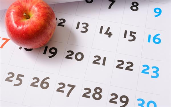 calendar with apple sitting on desk