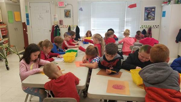 students create art projects in classroom
