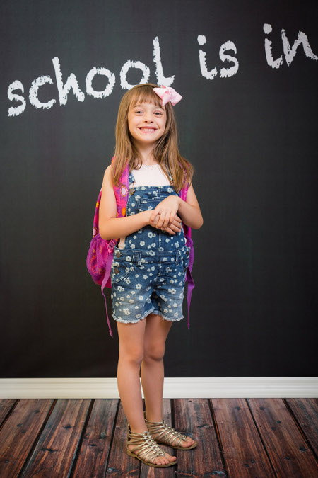student posing with backpack for back to school